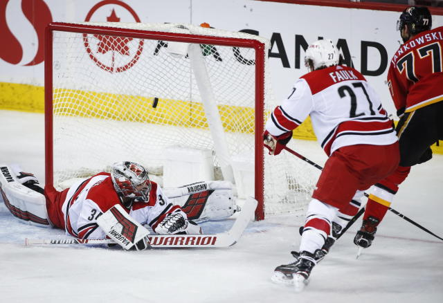 Carolina Hurricanes goalie Petr Mrazek, left, of the Czech Republic, lets in a goal from Calgary Flames' Mark Jankowski, right, during second period NHL hockey action in Calgary, Tuesday, Jan. 22, 2019. (Jeff McIntosh/The Canadian Press via AP)