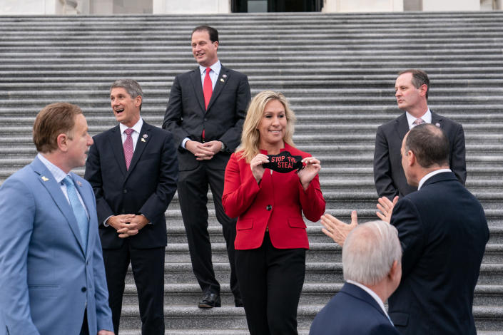 """Rep. Marjorie Taylor Greene (R-Ga.) shows off her """"Stop the Steal"""" face mask during a photo opportunity with House Minority Leader Kevin McCarthy for freshman congress members, on the steps of the Capitol in Washington, Jan. 4, 2021. (Anna Moneymaker/The New York Times)"""