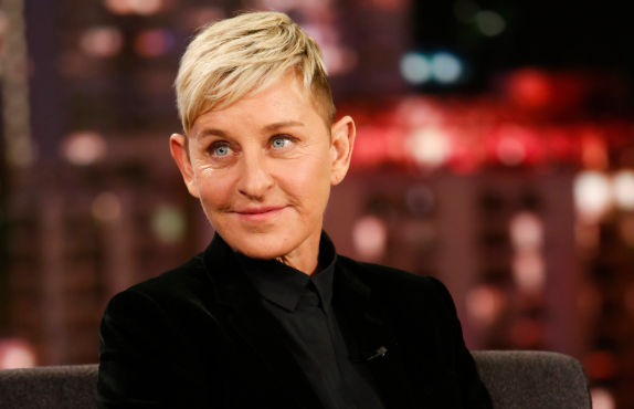 Ellen Degeneres smiles as she sits down and wears jeans and black blazer