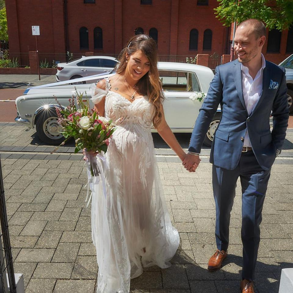 Tracey Jewel holds hands with her husband in her wedding dress