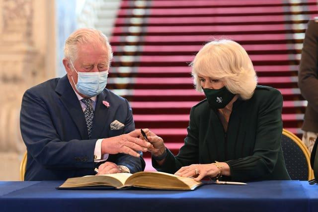 Charles and Camilla sign the visitors' book at Belfast City Hall