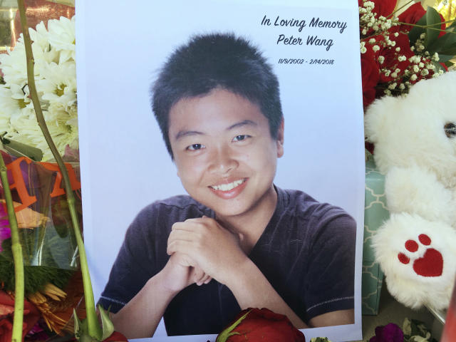 "<p>Student Peter Wang is seen in this photo near a memorial in Parkland, Fla., Friday, Feb. 16, 2018. (Photo: Allen Breed/AP)<br></p><p>Peter Wang died wearing his gray ROTC shirt and was last seen holding a door open for other students, his cousins Lin Chen and Aaron Chen told local news outlets. ""He doesn't care about popularity. He always liked to cheer people up. He is like the big brother everyone wished they had,"" said Lin Chen. She told the Sun Sentinel that Wang had two brothers, ages 11 and 5, and his parents, too upset to talk, own a restaurant in West Palm Beach, Fla. They had planned to celebrate Chinese New Year's eve Thursday. (AP) </p>"