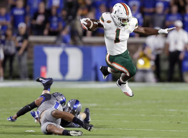 "Miami's <a class=""link rapid-noclick-resp"" href=""/ncaaf/players/252697/"" data-ylk=""slk:Mark Walton"">Mark Walton</a>, right, jumps over Duke's <a class=""link rapid-noclick-resp"" href=""/ncaaf/players/255216/"" data-ylk=""slk:Ben Humphreys"">Ben Humphreys</a> and <a class=""link rapid-noclick-resp"" href=""/ncaaf/players/228593/"" data-ylk=""slk:Bryon Fields Jr."">Bryon Fields Jr.</a> during the first half of an NCAA college football game in Durham, N.C., Friday, Sept. 29, 2017. (AP Photo/Gerry Broome)"