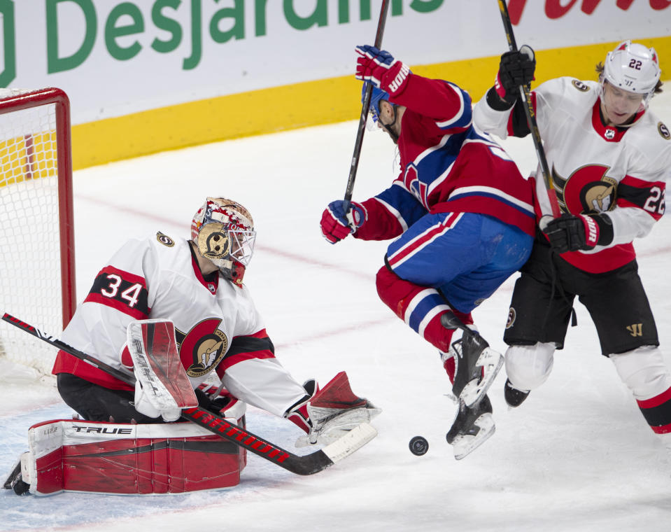 Ottawa Senators goaltender Joey Daccord (34) makes a save as Montreal Canadiens left wing Tomas Tatar (90) works against Senators defenseman Nikita Zaitsev (22) during the first period of an NHL hockey game Tuesday, March 2, 2021, in Montreal. (Ryan Remiorz/The Canadian Press via AP)