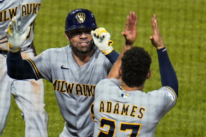 Milwaukee Brewers' Manny Pina, left, celebrates with Willy Adames (27) after hitting a two-run home run off Pittsburgh Pirates relief pitcher Austin Davis during the eighth inning of a baseball game in Pittsburgh, Thursday, July 29, 2021. (AP Photo/Gene J. Puskar)