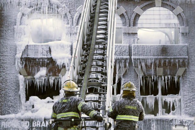 <p>Philadelphia firefighters work the scene of an overnight blaze in west Philadelphia, Feb. 16, 2015, as icicles form where water from their hoses has frozen. (Photo: Jacqueline Larma/AP) </p>