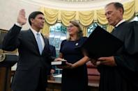 Mark Esper is sworn in as the new Secretary of Defense by Associate Justice Samuel Alito as Esper's wife Leah Esper holds the Bible as U.S. President Donald Trump looks on behind them in the Oval Office of the White House in Washington
