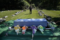 Siva Sriskanda takes a picture of the casket of James Brown, a friend and employee, after a short burial service at a cemetery in the Staten Island borough of New York, Thursday, June 17, 2021. Brown was buried with three others who died during the coronavirus pandemic and were being stored at a temporary morgue in Brooklyn. The facility is out of sight and mind for many as the city celebrates its pandemic progress but as a reminder of the loss, upheaval and wrenching choices the virus inflicted in one of its deadliest U.S. hotspots. (AP Photo/Seth Wenig)
