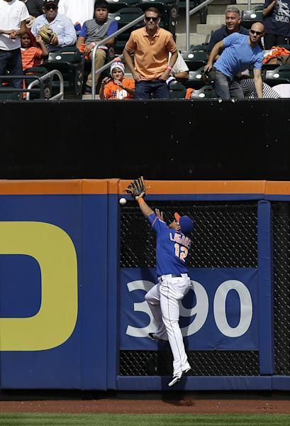 New York Mets center fielder Juan Lagares can't get his glove on a triple hit by Miami Marlins' Logan Morrison in the second inning of a baseball game at Citi Field Sunday, Sept. 15, 2013, in New York. (AP Photo/Seth Wenig)