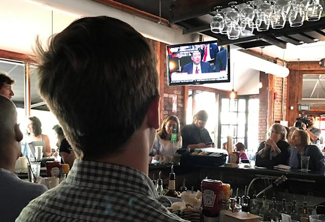 <p>People gather to watch former FBI director James Comey testify before the Senate Intelligence committee in Shaw's Tavern in Washington, June 8, 2017. (Gershon Peaks/Reuters) </p>