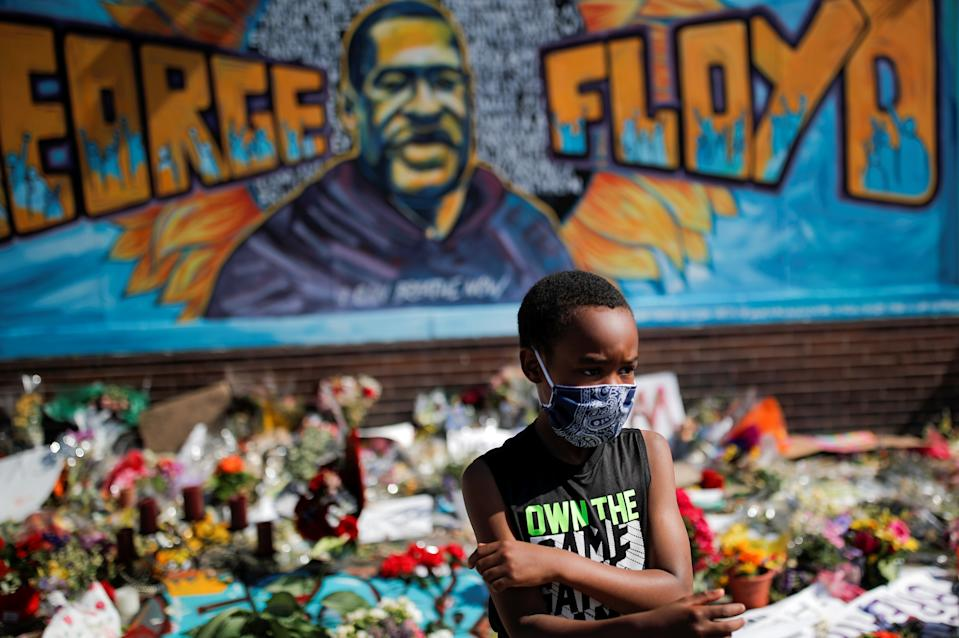 A child wears a protective mask at a makeshift memorial honoring George Floyd, at the spot where he was taken into custody, in Minneapolis, Minnesota, U.S., June 1, 2020.  REUTERS/Carlos Barria