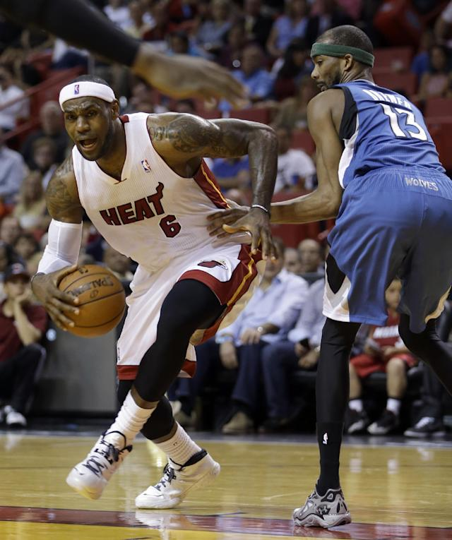 Miami Heat forward LeBron James (6) drives around Minnesota Timberwolves forward Corey Brewer (13) during the first half of an NBA basketball game in Miami, Friday, April 4, 2014. (AP Photo/Alan Diaz)