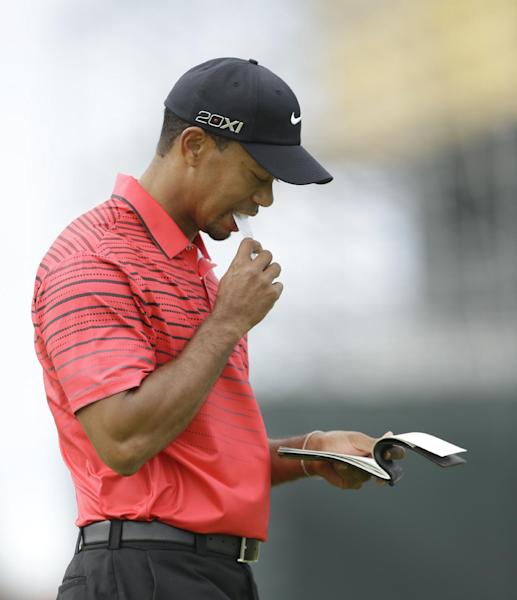 Tiger Woods of the United States checks his scorecard on the second green at Royal Lytham & St Annes golf club during the final round of the British Open Golf Championship, Lytham St Annes, England Sunday, July 22, 2012. (AP Photo/Jon Super)