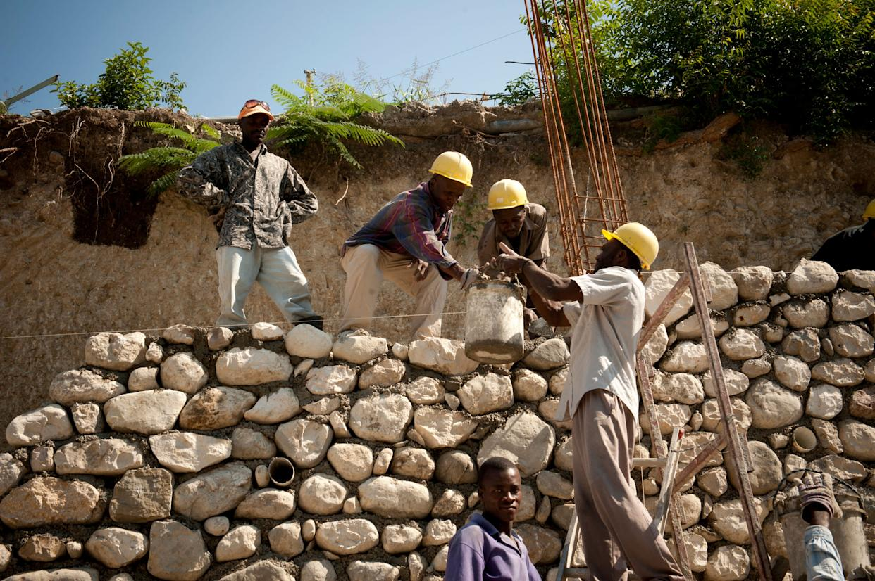 Construction workers pour cement while rebuilding a wall in Port-Au-Prince on April 12, 2011.