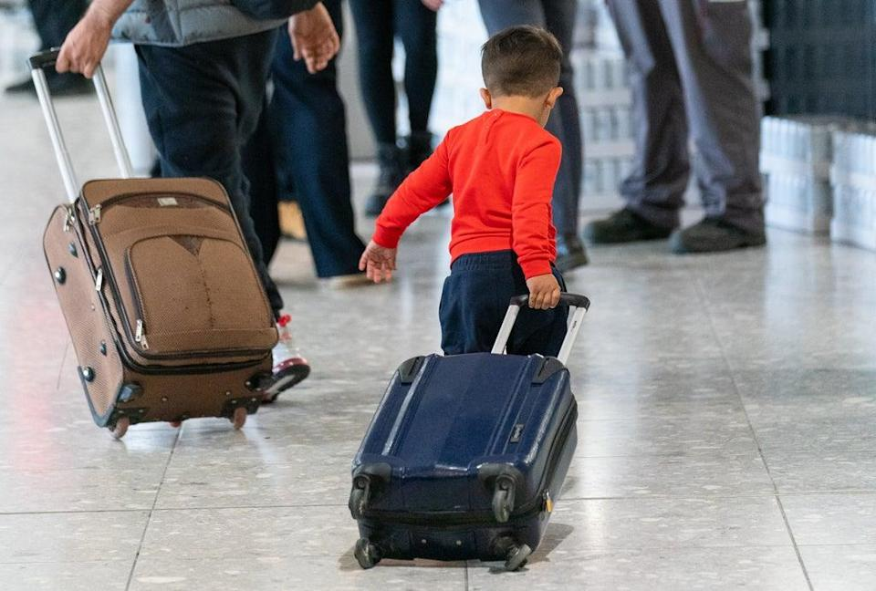 A young boy pulls his suitcase as refugees arrive at Heathrow from Afghanistan (Dominic Lipinski/PA) (PA Wire)