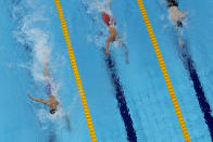 Robert Finke, left, of the United States, swims win the gold medal ahead of silver medalist Mykhailo Romanchuk, of Ukraine, and bronze medalist Florian Wellbrock, right, of Germany, in the men's 1500-meter freestyle final at the 2020 Summer Olympics, Sunday, Aug. 1, 2021, in Tokyo, Japan. (AP Photo/Jeff Roberson)