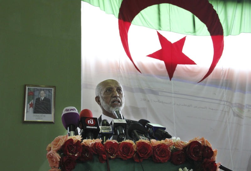 Abdelaziz Belkhadem, head of Algeria's most powerful political party, the National Liberation Front, is back-dropped by a large national flag as he addresses supporters at a rally in Algiers, Sunday May 6, 2012, on the final day of campaigning ahead of Algeria's elections. Algerians are gearing up for legislative elections on upcoming Thursday and the government is urging people to vote to avoid the low turnouts of past contests.  (AP Photo/Paul Schemm)