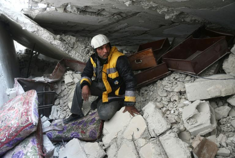 Forty-five-year-old Samir Salim, who along with his three brothers are members of the White Helmets rescue forces, sits in the rubble of his home in the town of Medeira in Syria's rebel-held Eastern Ghouta area on February 12, 2018