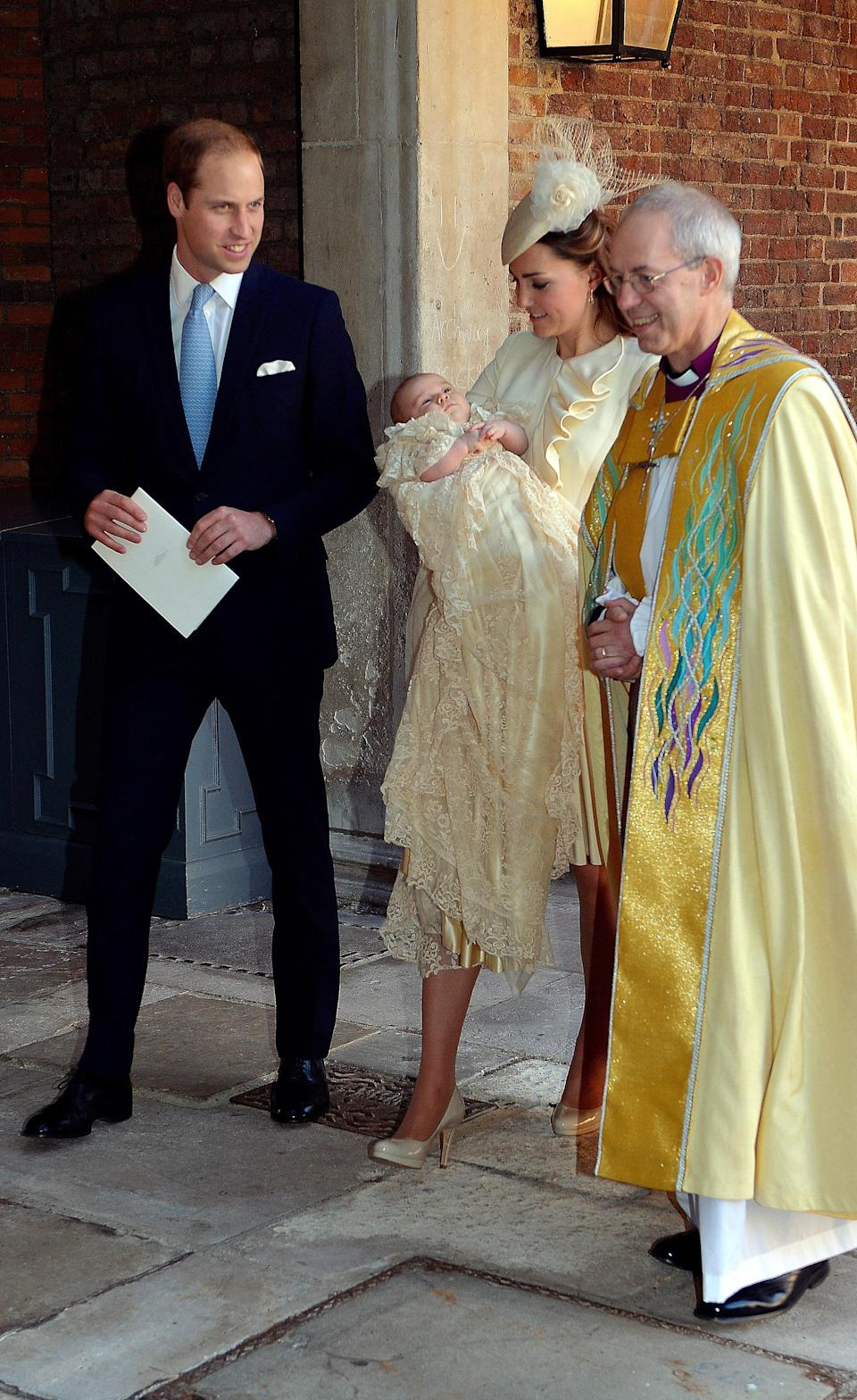 The Duchess of Cambridge carries her son Prince George with the Duke of Cambridge as they leave the Chapel Royal following the christening with Archbishop of Canterbury, Justin Welby. [Photo: Getty]