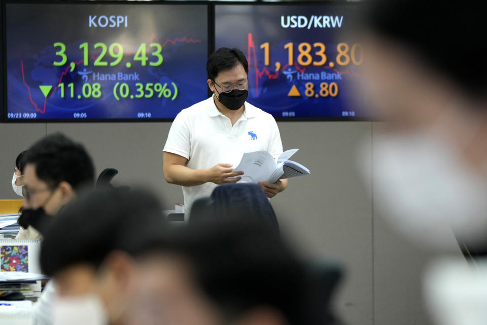 A currency trader passes by screens showing the Korea Composite Stock Price Index (KOSPI), left, and the exchange rate of South Korean won against the U.S. dollar at the foreign exchange dealing room of the KEB Hana Bank headquarters in Seoul, South Korea, Thursday, Sept. 23, 2021. Asian shares were mostly higher on Thursday after the Federal Reserve signaled it may begin easing its extraordinary support measures for the economy later this year.(AP Photo/Ahn Young-joon)