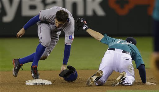 Texas Rangers' Ian Kinsler, left, is safe at second after stealing second base and avoiding the tag of Seattle Mariners second baseman Dustin Ackley, right, during a baseball game, Friday, April 12, 2013, in Seattle. (AP Photo/Ted S. Warren)