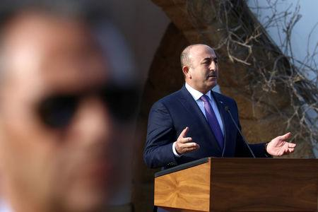 Turkey's Foreign Minister Mevlut Cavusoglu speaks to the media while a guard looks on during a visit in Nicosia