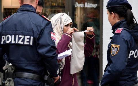 Police officers ask a woman to unveil her face in Zell am See, Austria - Credit: BARBARA GINDL/AFP/Getty Images