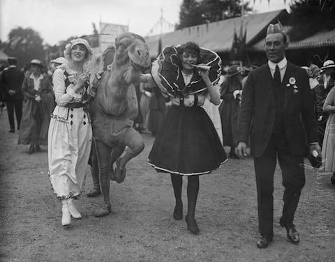 Fun and games at Kew Gardens. Yes, that is a camel - Credit: Topical Press Agency