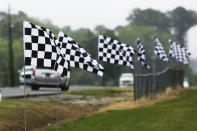 Checkered flags line a street outside Darlington Raceway Sunday, May 17, 2020, in Darlington, S.C. NASCAR, which has been idle since March 8 because of the coronavirus pandemic, makes its return with the Real Heroes 400 Nascar Cup Series auto race Sunday. (AP Photo/Brynn Anderson)
