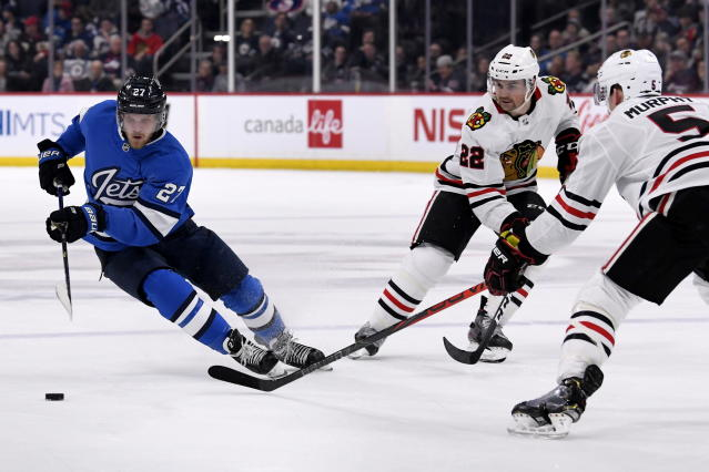 Winnipeg Jets' Nikolaj Ehlers (27) carries the puck past Chicago Blackhawks' Ryan Carpenter (22) and Connor Murphy (5) during second period NHL hockey action in Winnipeg, Manitoba on Sunday, Feb. 9, 2020. (Fred Greenslade/The Canadian Press via AP)