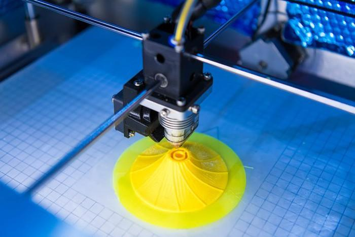 A 3D printer printing a yellow plastic object.