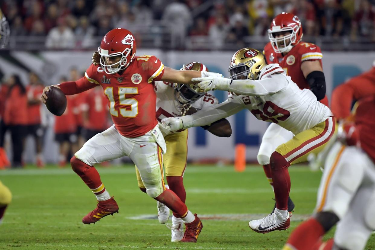 Kansas City Chiefs' quarterback Patrick Mahomes, left, tries to scramble away from San Francisco 49ers' Dee Ford, center, and DeForest Buckner, right, during the second half of the NFL Super Bowl 54 football game Sunday, Feb. 2, 2020, in Miami Gardens, Fla. (AP Photo/Mark J. Terrill)