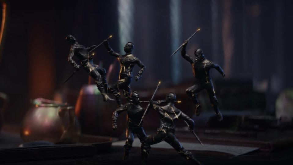 Miniatures fight each other on a desk in Loki