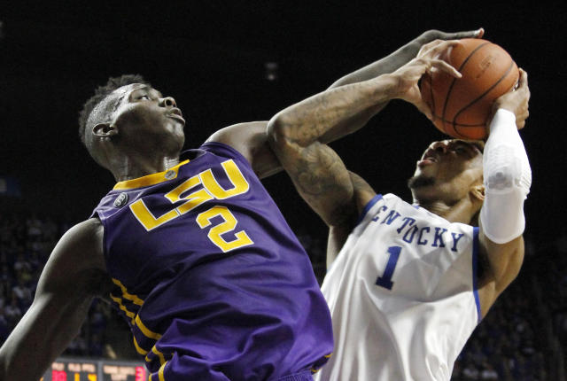 LSU's Johnny O'Bryant III (2) fouls Kentucky's James Young (1) during overtime in an NCAA college basketball game, Saturday, Feb. 22, 2014, in Lexington, Ky. Kentucky won 77-76. (AP Photo/James Crisp)