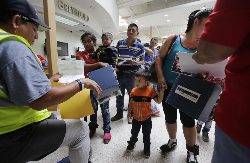 Immigrant families seeking asylum stand in line at the bus station after they were processed and released by U.S. Customs and Border Protection on June 29, 2018, in McAllen. (Photo: Eric Gay/AP)