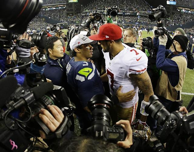 Seattle Seahawks' Russell Wilson, left, talks to San Francisco 49ers' Colin Kaepernick (7) after the NFL football NFC Championship game Sunday, Jan. 19, 2014, in Seattle. The Seahawks won 23-17 to advance to Super Bowl XLVIII. (AP Photo/Matt Slocum)