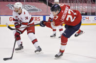 Florida Panthers center Eetu Luostarinen (27) takes a shot against Carolina Hurricanes defenseman Jaccob Slavin (74) during the second period of an NHL hockey game, Monday, March 1, 2021, in Sunrise, Fla. (AP Photo/Wilfredo Lee)