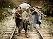 <p>A British soldier marches a wounded German along a railway track in 1916. (Tom Marshall/mediadrumworld.com) </p>