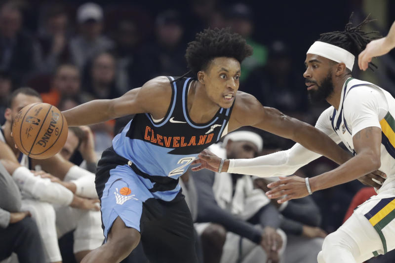 """FILE - In this March 2, 2020, file photo, Cleveland Cavaliers' Collin Sexton, left, drives past Utah Jazz's Mike Conley in the first half of an NBA basketball game in Cleveland. When Sexton learned that the NBA _ and not a virus _ had ended his second season, the Cavaliers guard had a guttural reaction. """"I was sick,"""" he said. The league's decision to only invite 22 teams to resume play at Disney World in Florida next month was a body blow for players on the omitted squads _ aka the Delete 8. And although they've had time to process the exclusion, Sexton, Cavs star forward Kevin Love and their teammates, are still struggling with the reality that their season is over. (AP Photo/Tony Dejak, File)"""
