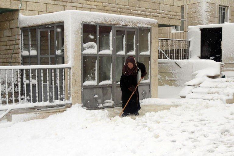 A Palestinian woman shovels in front of a building on January 10, 2013 in Tuqua, near the West Bank City of Bethlehem