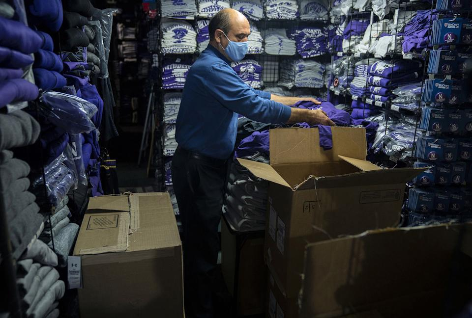 "David Haghnaji, owner of Campus Gear in downtown Evanston, Ill., stocks another of his locations—The Locker Room, across from Ryan Field—with new Northwestern gear on Oct. 15, 2020.<span class=""copyright"">E. Jason Wambsgans—Chicago Tribune/TNS/Sipa USA</span>"