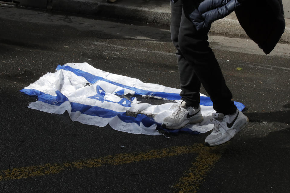 A demonstrator walks on an Israeli flag during a banned protest in support of Palestinians in the Gaza Strip, Saturday, May, 15, 2021 in Paris. Marches in support of Palestinians in the Gaza Strip were being held Saturday in a dozen French cities, but the focus was on Paris, where riot police got ready as organizers said they would defy a ban on the protest. (AP Photo/Michel Euler)