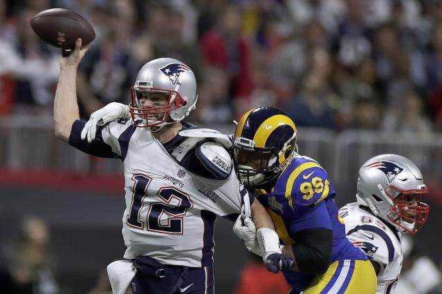 """File-This Feb. 3, 2019 file photo shows New England Patriots' Tom Brady (12) passing under pressure form Los Angeles Rams' Aaron Donald (99) during the first half of the NFL Super Bowl 53 football game in Atlanta. Brady will soon slip on his sixth Super Bowl ring, and Herb Adderley is the only other man on the planet who can relate to that level of success as the National Football League celebrates its 100th season. """"It's going to be a long time, another 100 years, before somebody wins himself six titles,"""" said Adderley, the Hall of Fame cornerback for Vince Lombardis great Green Bay Packers teams of the 1960s. (AP Photo/Carolyn Kaster, File)"""