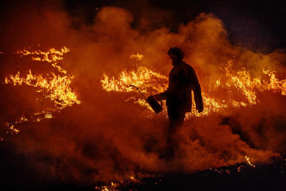 A firefighter works to douse flames of a bushfire in Australia.