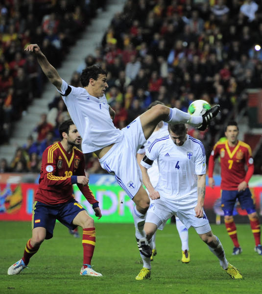 Finland's Roman Eremenko, front, duels for the ball with Spain's Cesc Fabregas, left, during a Group I 2014 World Cup qualifying soccer match, at El Molinon stadium in Gijon, northern Spain on Friday, March 22, 2013. (AP Photo/Alvaro Barrientos)