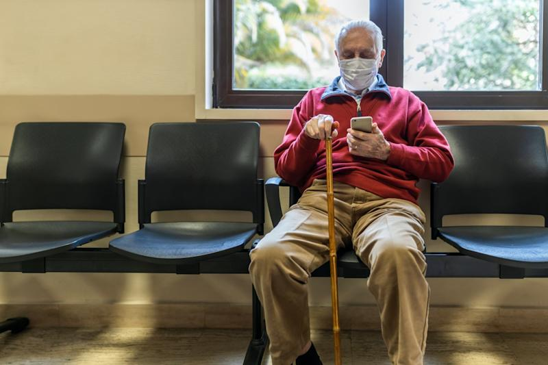 elderly man sitting at the doctor's office in a hospital with respirator and using his smart phone
