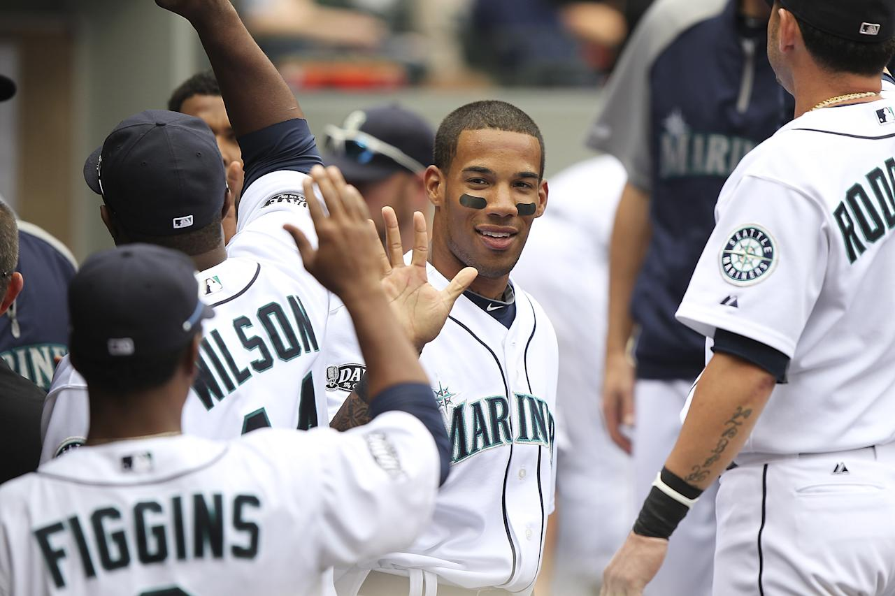 SEATTLE - JUNE 05:  Greg Halman #56 of the Seattle Mariners is congratulated by teammates after scoring in the third inning against the Tampa Bay Rays at Safeco Field on June 5, 2011 in Seattle, Washington. (Photo by Otto Greule Jr/Getty Images)