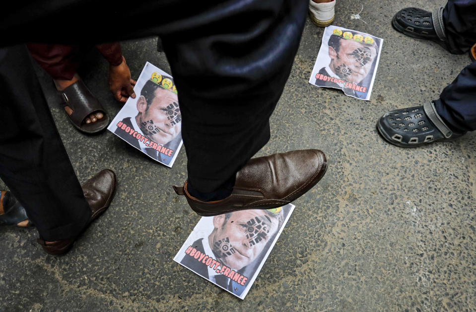 A Muslim activist stamps on posters bearing defaced images of French President Emmanuel Macron during a protest near the French Consulate, in Kolkata, India, Saturday, Oct. 31, 2020. Muslims have been calling for both protests and a boycott of French goods in response to France's stance on caricatures of Islam's most revered prophet. (AP Photo/Bikas Das)