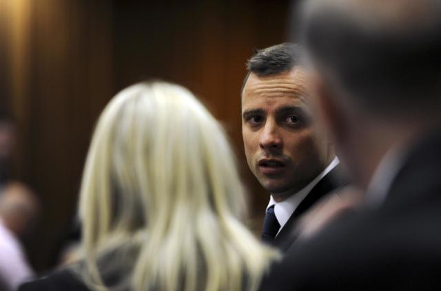 Olympic and Paralympic track star Oscar Pistorius speaks to members of his legal team during the fourth day of his trial for the murder of his girlfriend Reeva Steenkamp at the North Gauteng High Court in Pretoria, March 6, 2014. REUTERS/Werner Beukes/Pool (SOUTH AFRICA - Tags: SPORT ATHLETICS CRIME LAW)