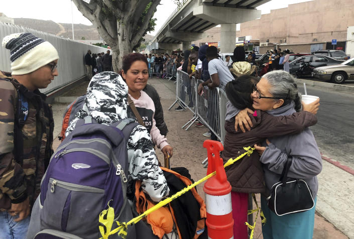 FILE - In this Thursday, Sept. 26, 2019, file photo, Luz Bertila Zazueta, 75, of Tijuana, right, hugs farewell to a Peruvian woman and her four children whose numbers were called to claim asylum at a border crossing in San Diego. A federal judge ruled Thursday, Sept. 2, 2021 that the U.S. government's practice of denying migrants a chance to apply for asylum on the Mexican border until space opens up to process claims is unconstitutional.(AP Photo/Elliot Spagat, File)